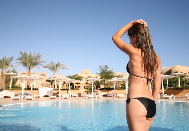 Meisje in bikini tegen toevlucht zwembad Gratis Foto