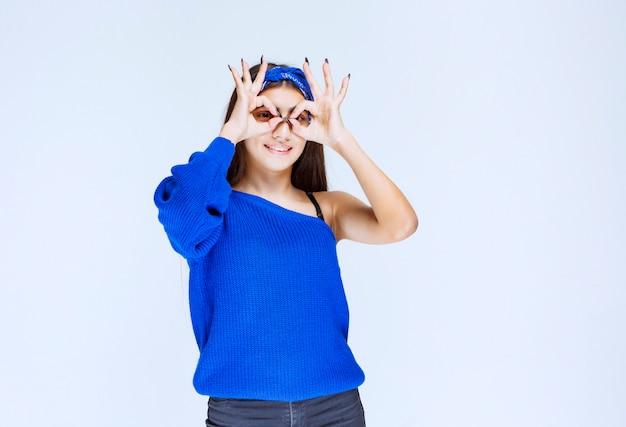 Meisje in blauw feestoverhemd dat over haar vingers kijkt.