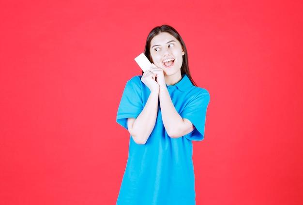 Meisje in blauw shirt dat haar visitekaartje presenteert en verrast en doodsbang wordt