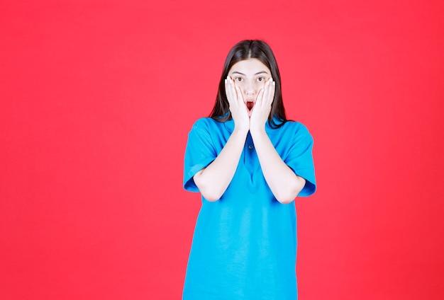 Meisje in blauw shirt dat op de rode muur staat en er bang en doodsbang uitziet