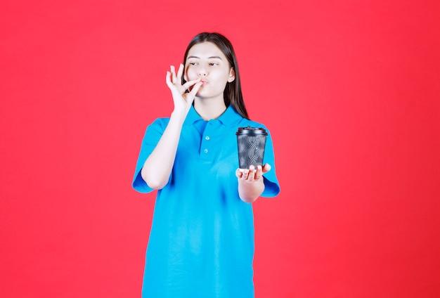 Meisje in blauw shirt met een zwarte wegwerpkoffiekop en genietend van de smaak.