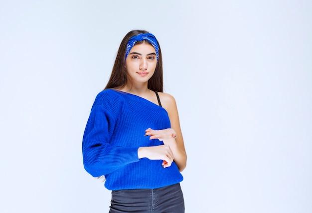 Meisje in blauw shirt wijst haar tijd en ziet er veeleisend uit.