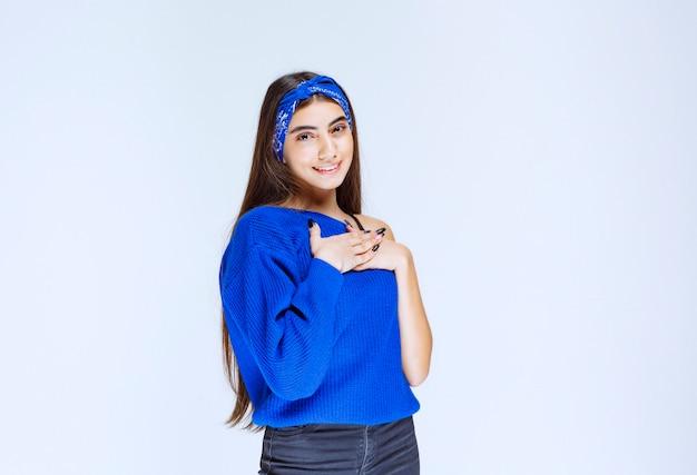 Meisje in blauw shirt wijzend op zichzelf.