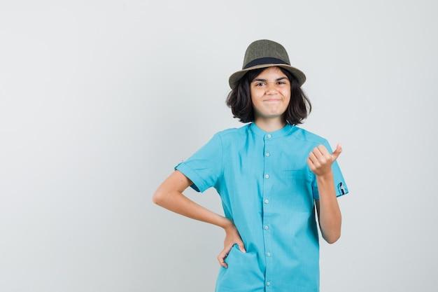 Meisje in blauw t-shirt, hoed die duim toont en vrolijk kijkt