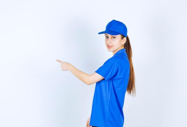 Meisje in blauw uniform dat naar de linkerkant wijst.