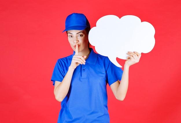 Meisje in blauw uniform en baret die een denkbord in de vorm van een wolk vasthoudt en om stilte vraagt.