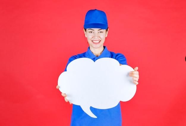 Meisje in blauw uniform en baret met een denkbord in de vorm van een wolk.