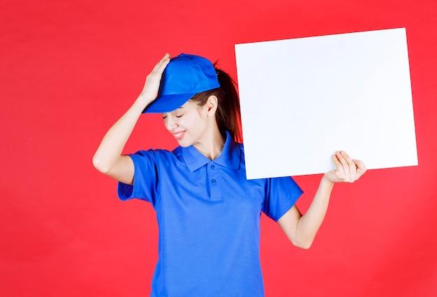 Meisje in blauw uniform en baret met een wit vierkant infobureau en ziet er verrast en attent uit.