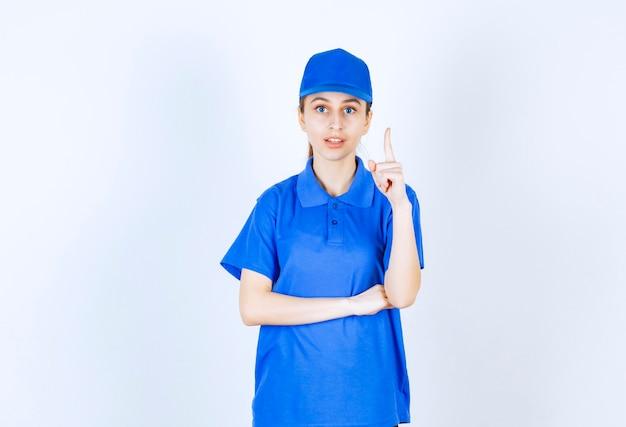 Meisje in blauw uniform wijzend op iets hierboven.
