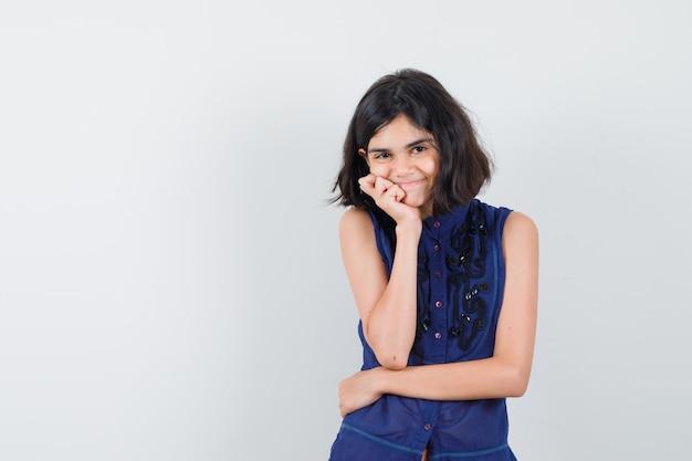 Meisje in blauwe blouse die zich in het denken bevindt stelt en positief kijkt