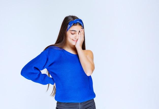 Meisje in blauwe feestjurk met hoofd terwijl ze verward en verrast is.