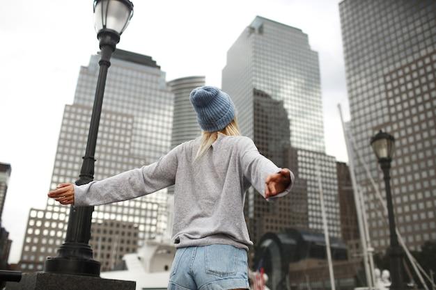 Meisje in blauwe hoed en grijze trui staat op straat met wolkenkrabbers