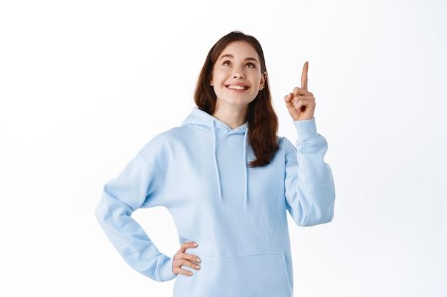 Meisje in blauwe hoodie wijzend en omhoog kijkend naar promo-logo, tevreden glimlachend, goede reclame tonend, staande tegen een witte muur