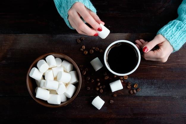 Meisje in blauwe trui met kopje koffie en pittimg een marshmallow erin handen close-up kom met marshmallows kopie ruimte
