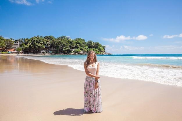 Meisje in bloemen roze maxirok die zich op de overzeese kust bevindt