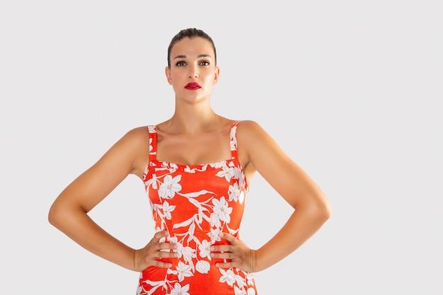 Meisje in bloemrijke jurk en vrolijk in felle kleuren poseren met haar handen op haar middel en recht vooruit kijken
