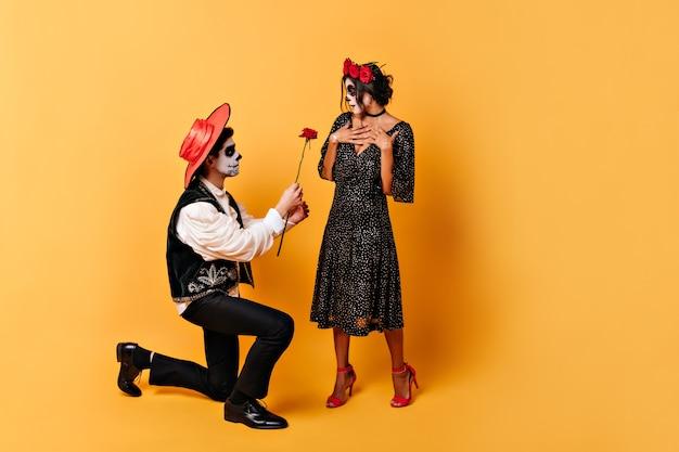 Meisje in bolletjesjurk met bloemen in het haar is aangenaam verrast door de daad van haar jonge man. man in sombrero geeft rode roos aan zijn vrouw.
