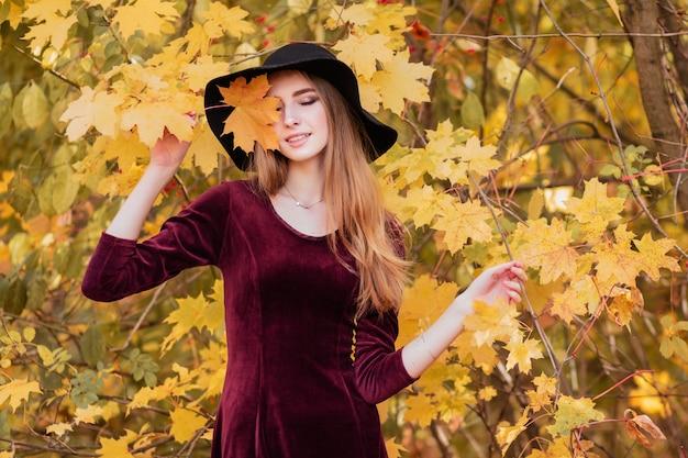 Meisje in bordeauxrode jurk en hoed in gele bladeren in de herfst