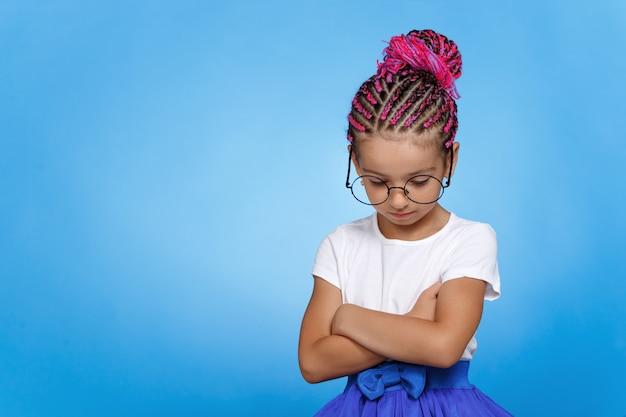 Meisje in brillen, wit overhemd en rok, droevig neerkijkend, met gekruiste handen, over blauwe ruimte.