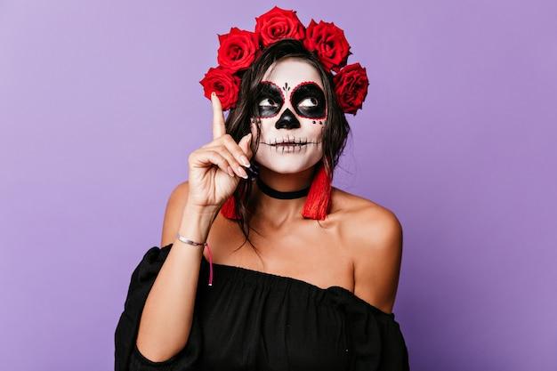 Meisje in carnavalskostuum kwam met een grappig idee. portret van vrouw met rozen in donker haar.