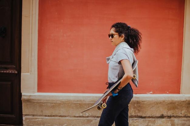Meisje in casual outfit bedrijf skateboard lopen