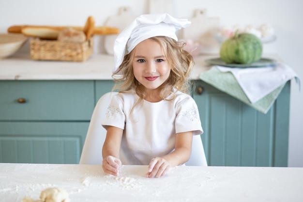 Meisje in chef-kokhoed bij keuken thuis
