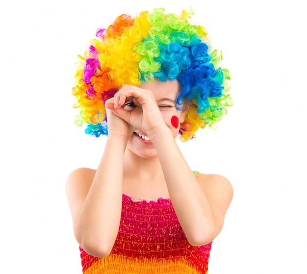 Meisje in clownpruik op witte achtergrond wordt geïsoleerd die