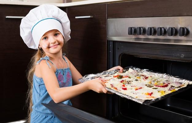 Meisje in cook cap in de buurt van de oven met pizza