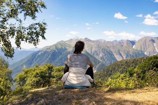 Meisje in de bergen kijkend naar het landschap, zittend op de top, uitzicht vanaf de achterkant