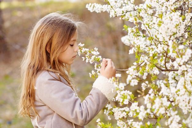 Meisje in de buurt van de bloeiende kersenboom