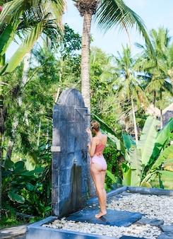 Meisje in de douche onder de blote hemel op de jungle-achtergrond