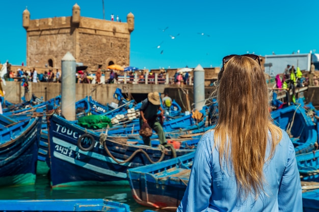 Meisje in de haven van essaouira. beroemde blauwe boten.