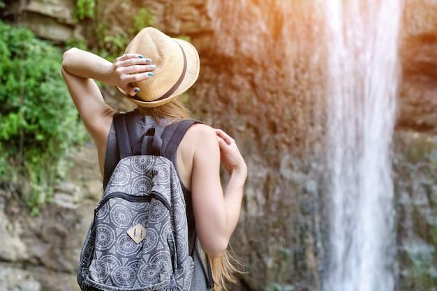Meisje in de hoed bewondert de waterval. uitzicht vanaf de achterkant
