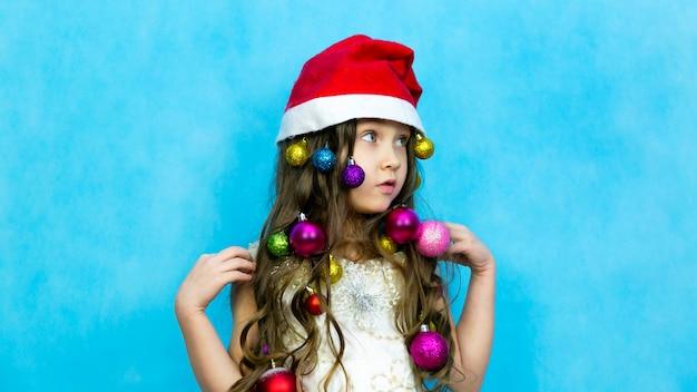 Meisje in de hoed van de kerstman op blauw