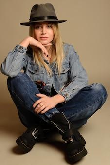 Meisje in de hoed van jeanslaarzen en jasjezitting