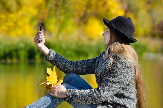 Meisje in de hoed zittend op de pier en maakt selfie
