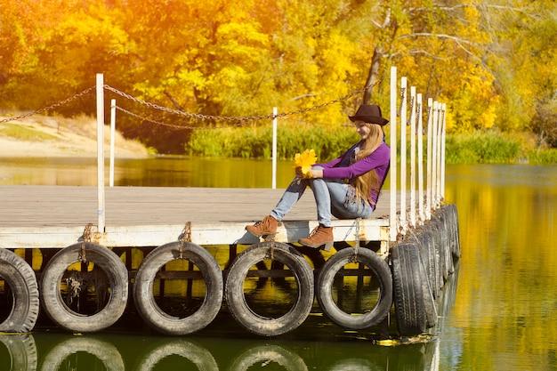 Meisje in de hoedenzitting op het dok door de rivier