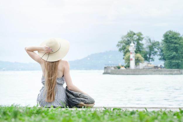 Meisje in de hoedenzitting op het dok. zee en kleine vuurtoren in de verte. achteraanzicht