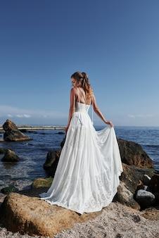 Meisje in de kleding van de huwelijksluxe het stellen op overzeese kust. bruid op rotsen.