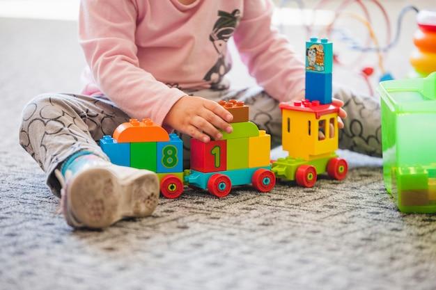 Meisje in de kleuterschool met speelgoed