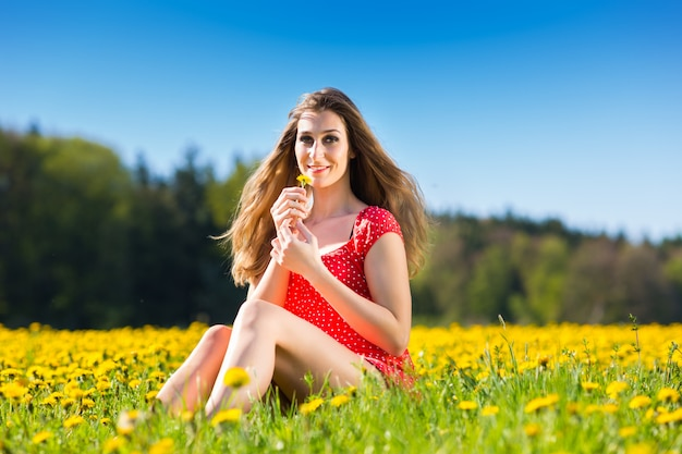 Meisje in de lente op een bloemweide met paardebloem