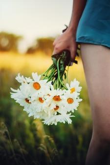 Meisje in de natuur met een boeket van madeliefjes in de hand. concept van romantiek en liefde