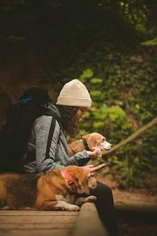 Meisje in de natuur rusten met haar honden kijken naar de mobiel.