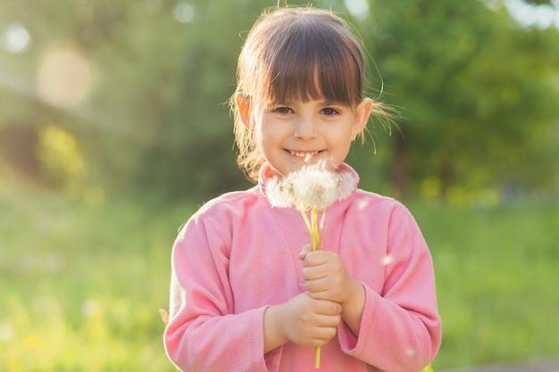 Meisje in de natuur verzamelt snuifjes en blaast op paardebloemen Premium Foto