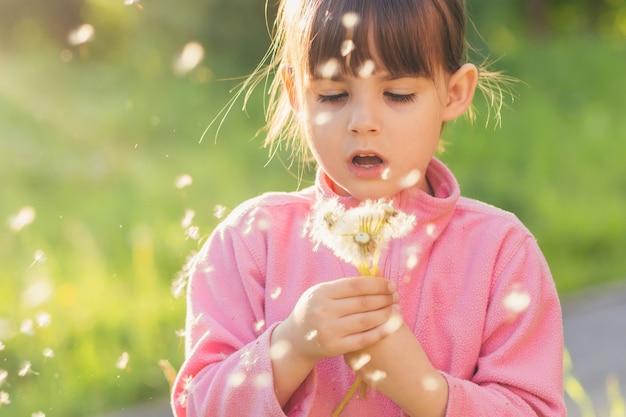 Meisje in de natuur verzamelt snuifjes en blaast op paardebloemen