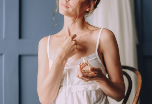 Meisje in de ochtend gebruikt een parfum om haar nek