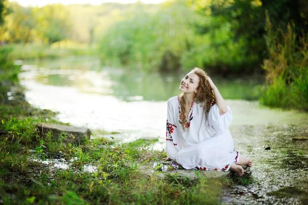 Meisje in de oekraïense nationale kleding met kransen van bloemen op de rivieroever