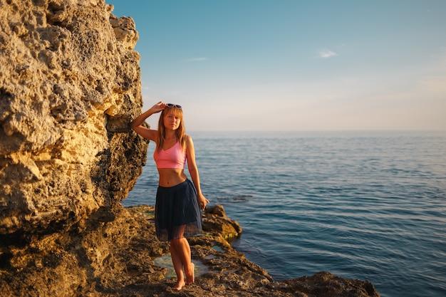 Meisje in de rotsen op het overzees bij zonsondergangdag