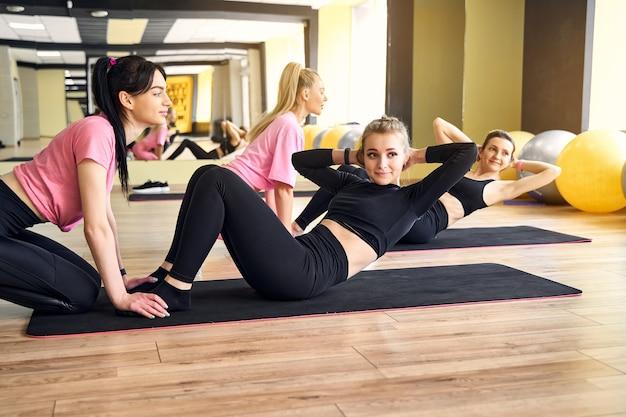 Meisje in de sportschool doen oefeningen voor het pers-teamwerk Premium Foto