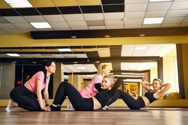 Meisje in de sportschool doen oefeningen voor het pers-teamwerk